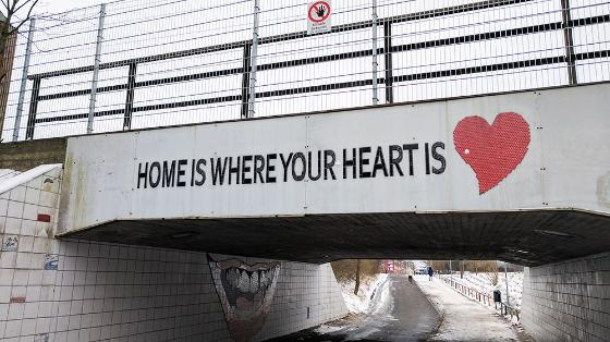 "An underpass with the words ""Home is where your heart is"" is spray-painted. Picture"