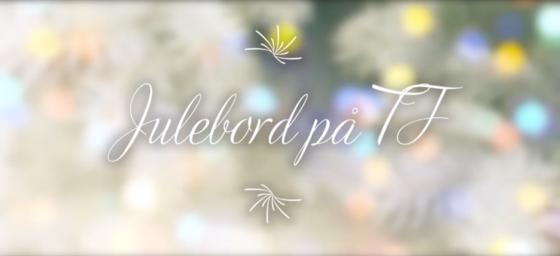 """Illustrerende logo for eventet. I bakgrunnen er det et ufokusert bilde av to juletrær med flerfargede lys. Over dette ligger teksten """"Julebord på TF"""" i en elegant og kursiv font."""